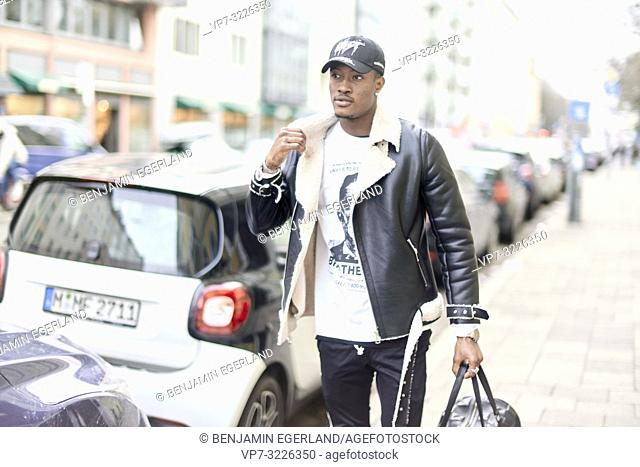 young fashionable man walking at pavement next to cars in city, streetstyle fashion, in Munich, Germany