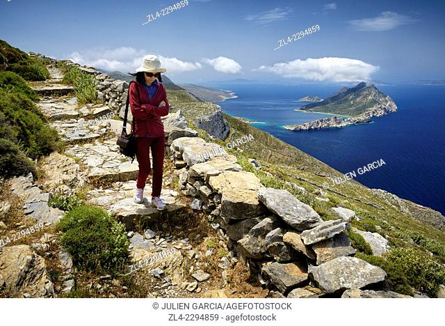 Woman walking on the historical hiking trail going from the Panagia Hozoviotissa monastery to Aegiali village, Nikouria island in the distance