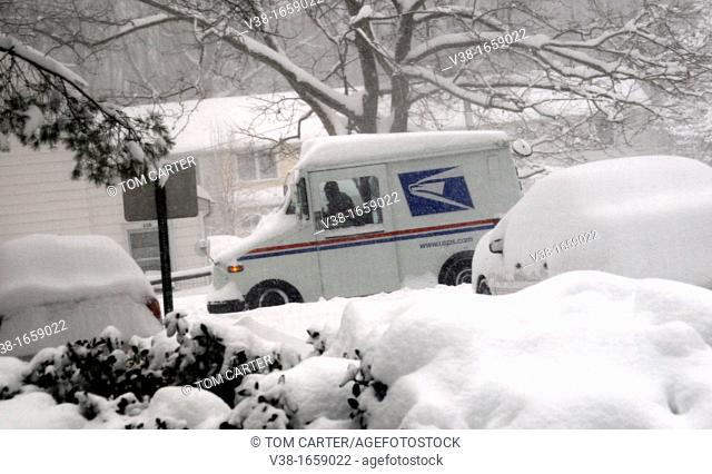 mail truck passes mound of snow covered cars during a blizzard in Greenbelt, Maryland