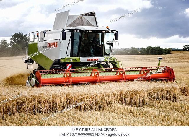 10 July 2018, Germany, Sarkwitz:A combine harvests winter barley. The Schleswig-Holstein Champer of Agriculture reports that this year's grain and rapeseed...