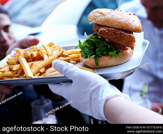 31 July 2020, Berlin: A waitress at The Haus restaurant serves burgers and fries with gloves during the Corona crisis. Photo: Annette Riedl/dpa-Zentralbild/ZB
