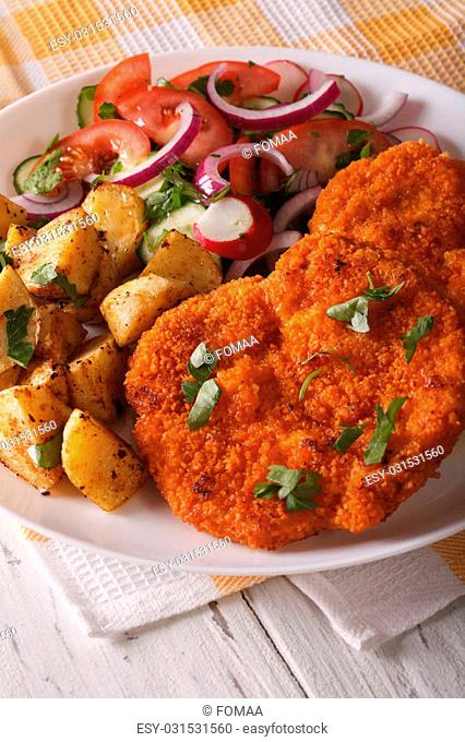 Wiener schnitzel, fried potatoes and vegetable salad on the plate closeup. vertical