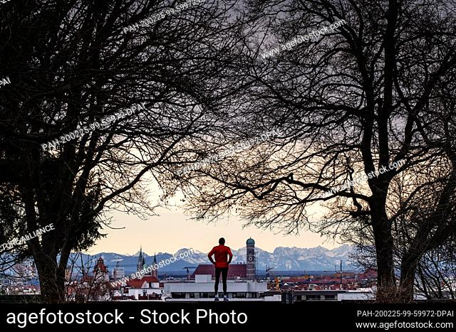 dpatop - 25 February 2020, Bavaria, Munich: A jogger stands on Luitpold Hill in the Schwabing district and looks over the backdrop of the Bavarian capital