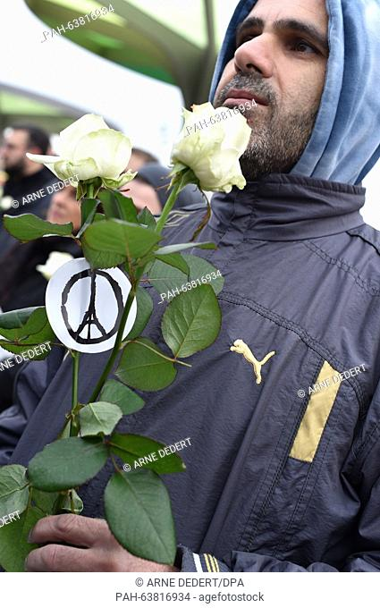 A man wearing a beanie featuring a peace sign who is carrying a white rose attends a commemorative rally for the victims of the Paris terror attacks