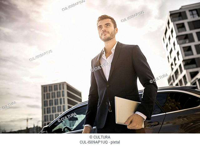 Low angle view of young businessman on street carrying digital tablet