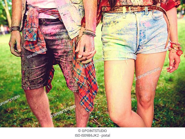 Waist down view of young couple covered in coloured chalk powder at festival