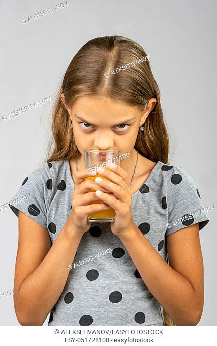 A ten year old girl drinks juice and enjoys the scent