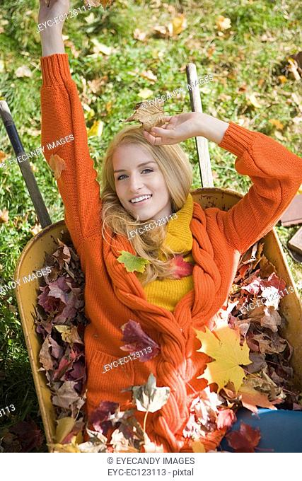 Young blonde woman lounging in wheelbarrow filled with autumn leaves