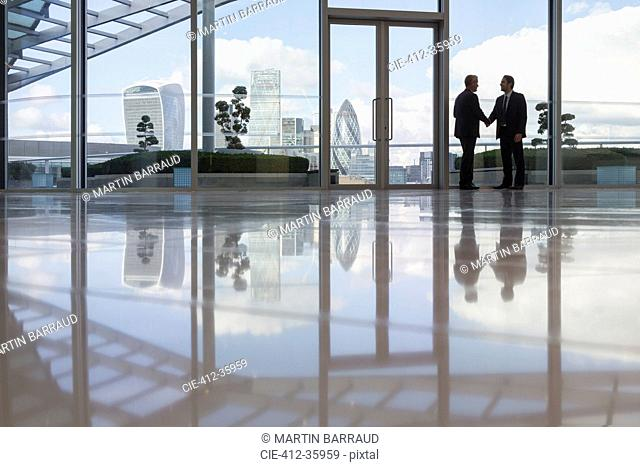 Businessmen handshaking in highrise office with urban city view, London, UK