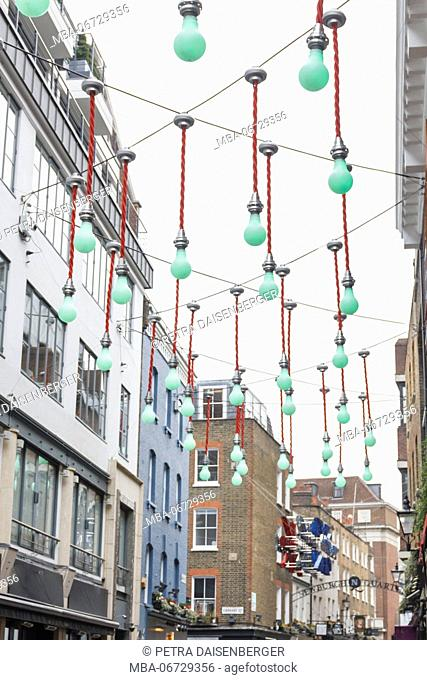 Green light bulbs decorate a shopping street in London