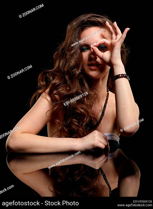 Beauty portrait of young woman sit at the black table. Brunette girl with long hair and evening female makeup on black background. OK finger sign
