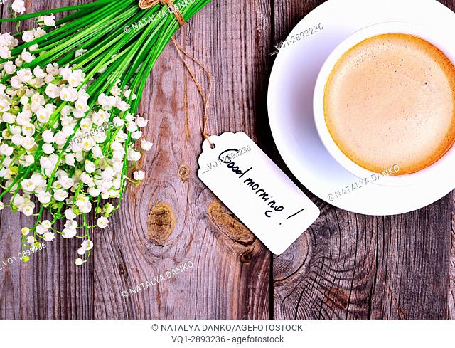Cup of cappuccino and a bouquet of white lilies of the valley on a gray wooden background, top view