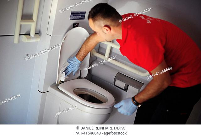 Sabit Musljija cleans a toilet in an Intercity Express (ICE) in Frankfurt Main, Germany, 06 August 2013. German railway company Deutsche Bahn (DB) will from now...