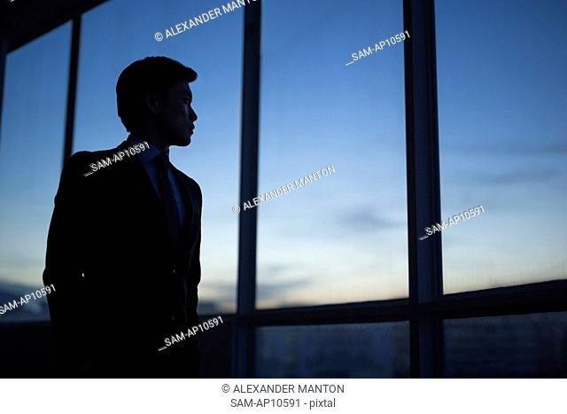 Singapore, Businessman standing by window at dusk