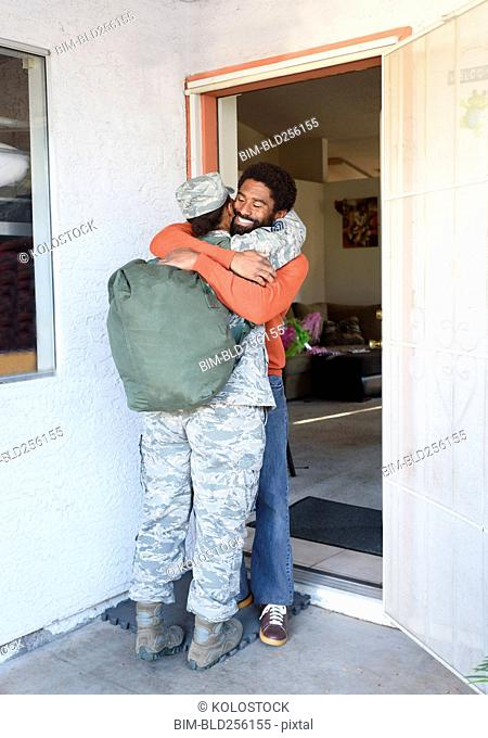 Black woman soldier hugging man in doorway