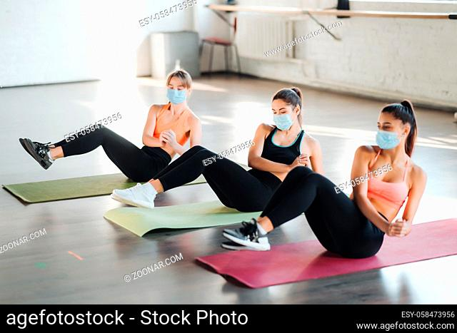Young women doing push up exercise in room during morning. Slim girls wearing masks to protect covid-19 disease pandemic and social distancing
