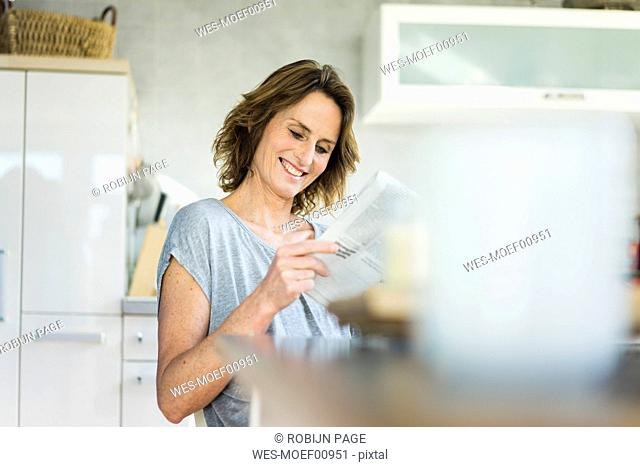 Smiling woman reading newspaper in kitchen at home