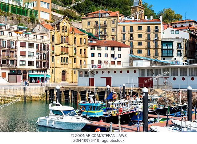 Picturesque houses, Fishing boats and sport fishing boats to recreational boat fishing are moored in the harbor of Donostia San Sebastian