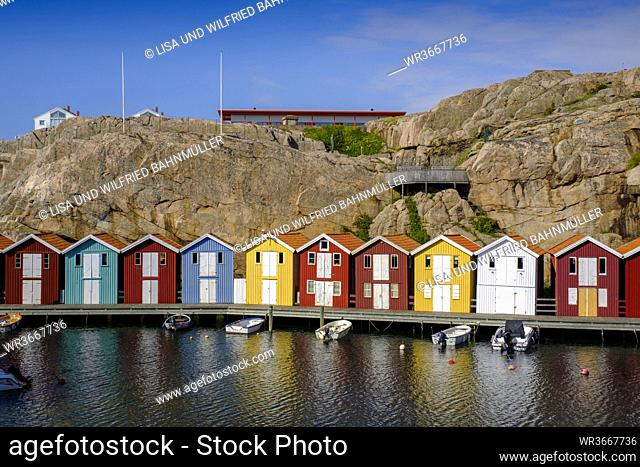 Sweden, Vastra Gotaland County, Smogen, Boats moored in front of colorful boathouses