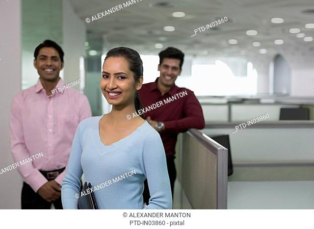 India, Smiling businesswoman in front of colleagues in office
