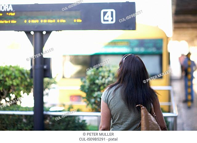 Rear view of woman strolling to railway platform