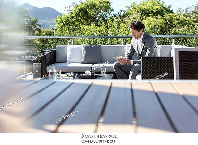 Businessman using digital tablet on sunny luxury balcony patio sofa