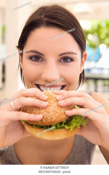 Asia, Thailand, Young woman eating hamburger, smiling, close-up, portrait