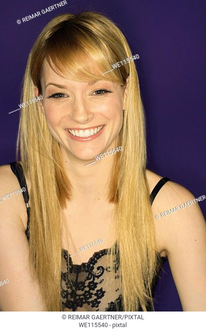 Smiling face of a blond woman in black lace chemise on a purple background