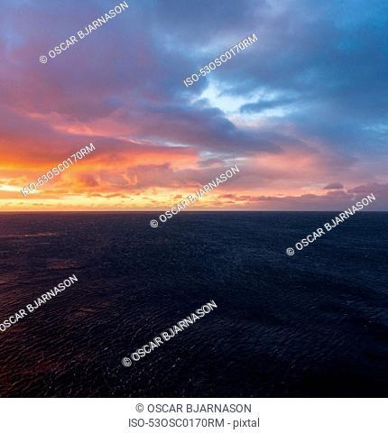 Sun rising over ocean in cloudy sky