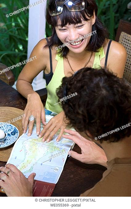 young couple having breakfast and planning for vacation