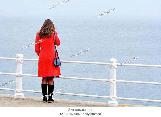 Woman with red coat with black boots sitting in front of sea. Young woman with red coat looking at winter landscape of frozen sea