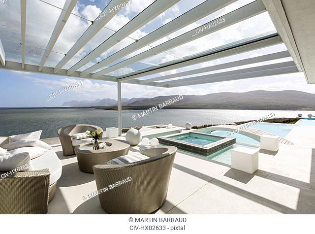 Sunny modern luxury patio with infinity pool and ocean view