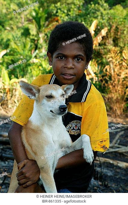 Boy holding a dog, Heldsbach, Papua New Guinea, Melanesia