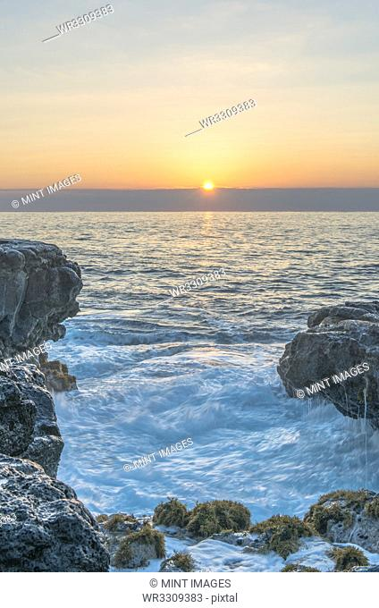 Sunrise over rock formations on beach