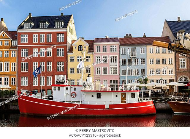 Moored boat and colourful 17th century apartment buildings and houses along the Nyhavn canal, Copenhagen, Denmark, Europe