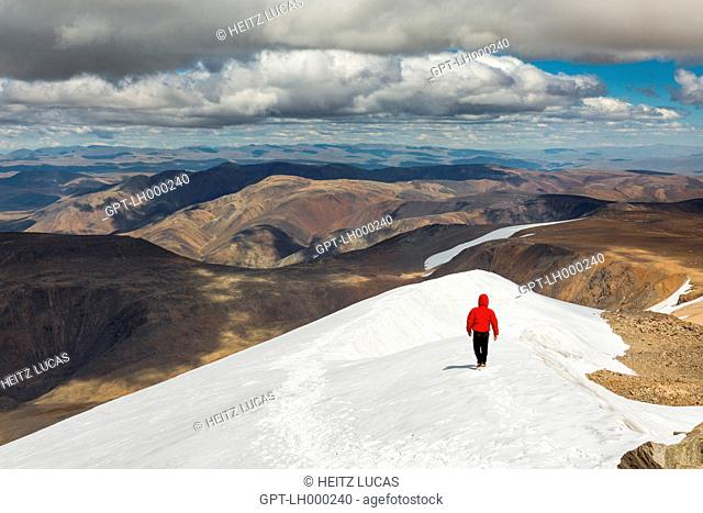 HIKER FOLLOWING A SNOW-COVERED SUMMIT, ARID MOUNTAINS IN THE DISTANCE, TAVAN BOGD MASSIF, ALTAI, BAYAN-OLGII PROVINCE, MONGOLIA