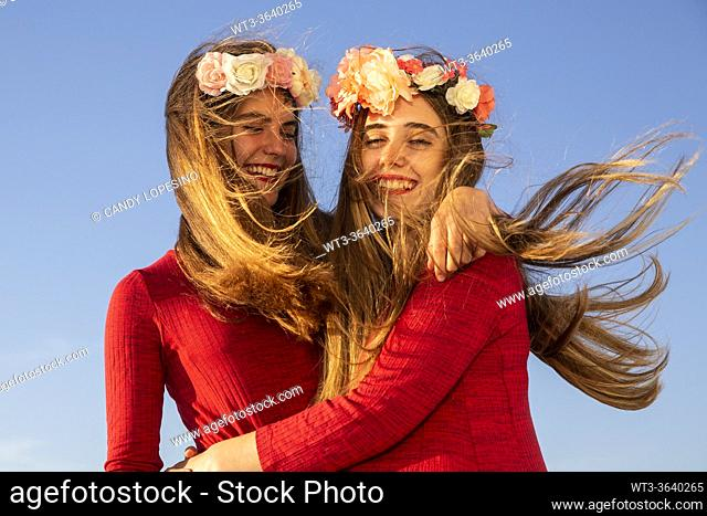 Two young girls with red dress and long blonde hair at the wind and roses having fun