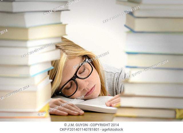 Student girl sleeping on desk between stacks of books