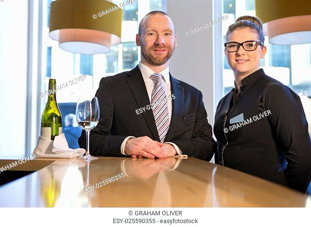 Bar manager with a member of staff. They are smiling for the camera with a bottle of champagne and a glass in front of them
