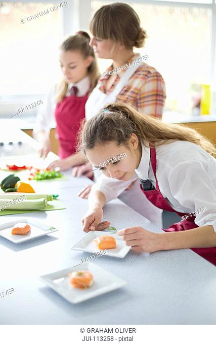 Focused high school student plating food in home economics class