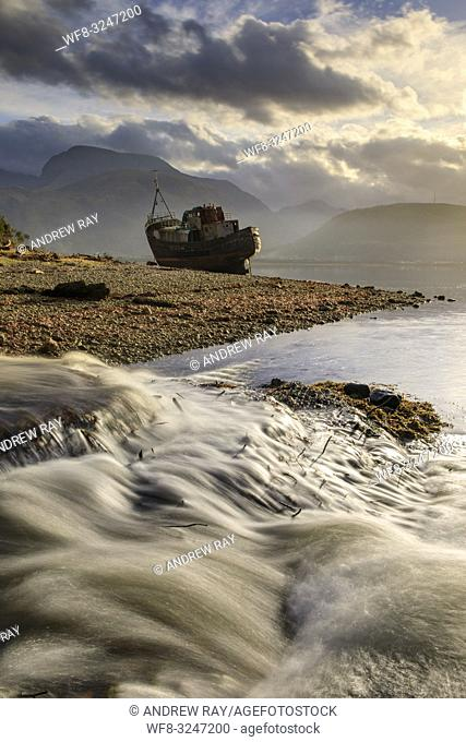 A waterfall and abandoned boat at Corpach in Scotland with Ben Nevis in the distance