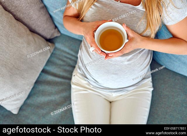 Top view of a young pregnant woman reclining on a comfortable sofa at home with a large mug of hot tea in a close up on her belly