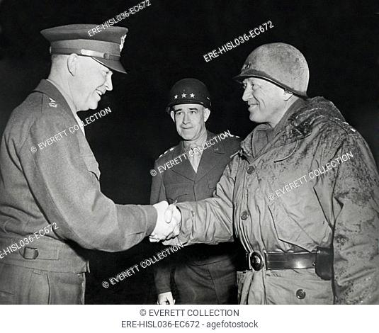 General Dwight Eisenhower shakes hands with Gen. George Patton at the front in 1945. Patton is in battle dress. Gen. Omar Bradley stands in the background