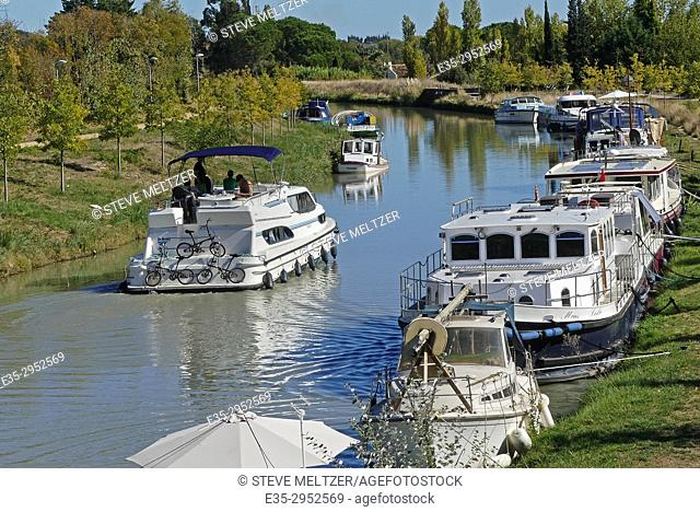 A rental powerboat motoring on the Canal du Midi, Capestang, France