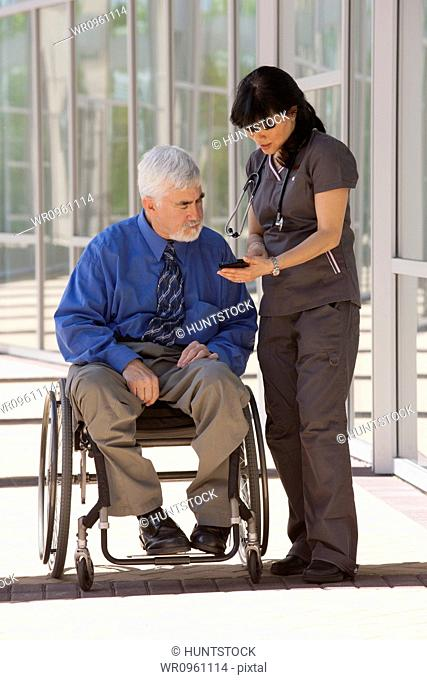Man with muscular dystrophy and diabetes in his wheelchair talking with nurse using smart phone