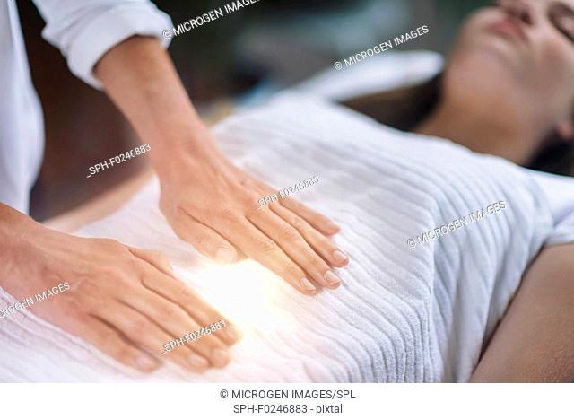 Female therapist holding hands over woman's stomach. Alternative therapy concept of stress reduction and relaxation