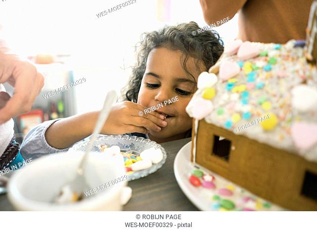 Little girl nibbling sweets for Christmas gingerbread house