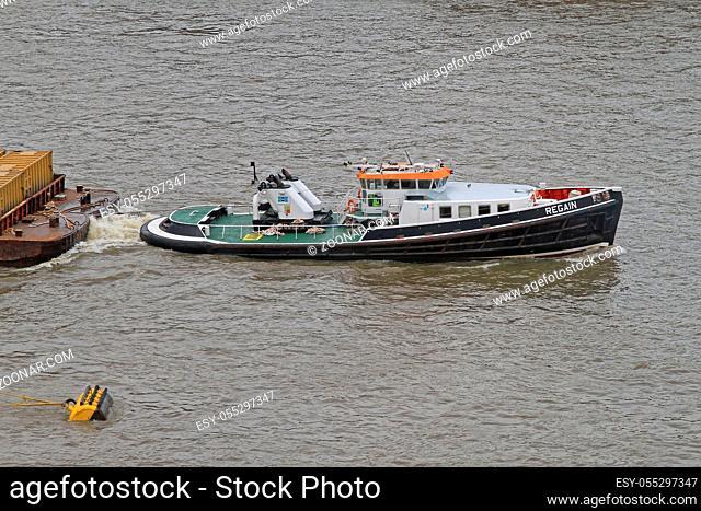 London, United Kingdom - April 03, 2010: Tugboat Pulling Barge at Thames River in London, UK