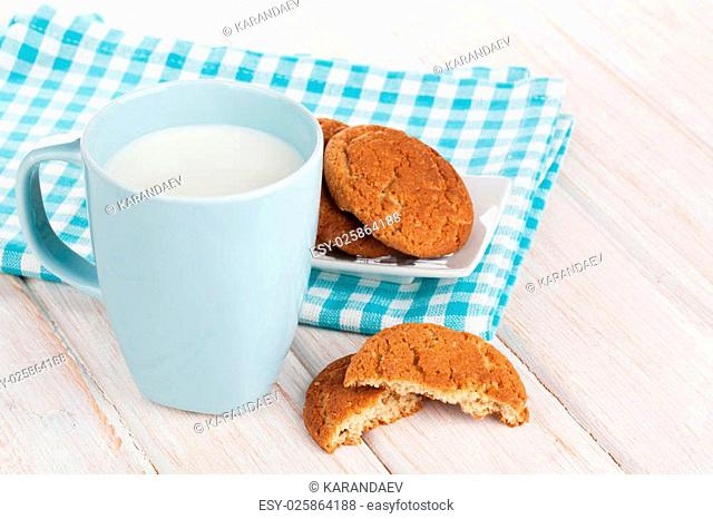 Cup of milk and gingerbread cookies on white wooden table