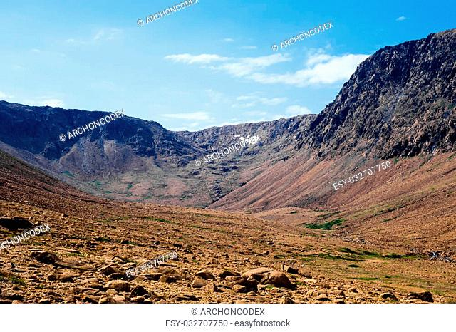 Dry rocky valley sloping between surrounding plateau cliffs and ridges under pale blue sky, at Tablelands, Gros Morne National Park, Newfoundland, Canada